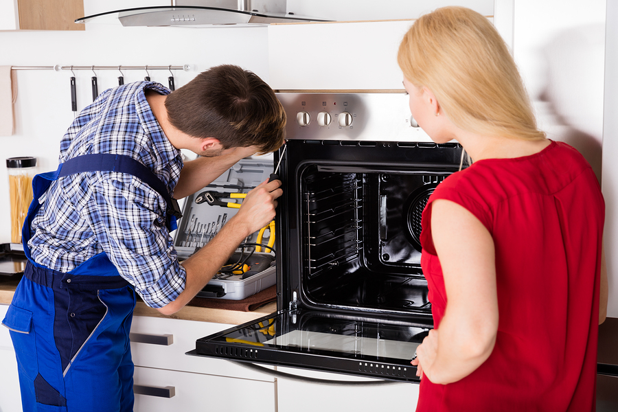 Male Worker Repairing Oven Appliance In Presence Of Young Woman In Kitchen Room